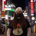 student in beanie and mask in the middle of dark street with lights in background.