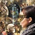 My friend Lin Li wearing and observing Venetian masks during Carnevale in Venice, Italy.
